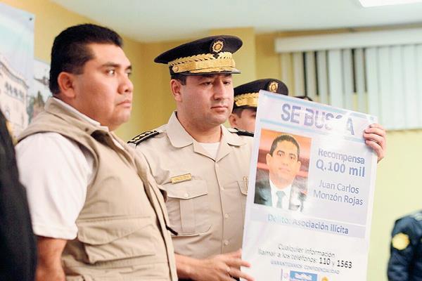 Elmer Sosa (izquierda), viceministro de Gobernación, entrega un afiche al director de la PNC, Walter René Velásquez Cerón, con la foto de Juan Carlos Monzón. (Fotografía Prensa Libre: Alvaro Interiano).