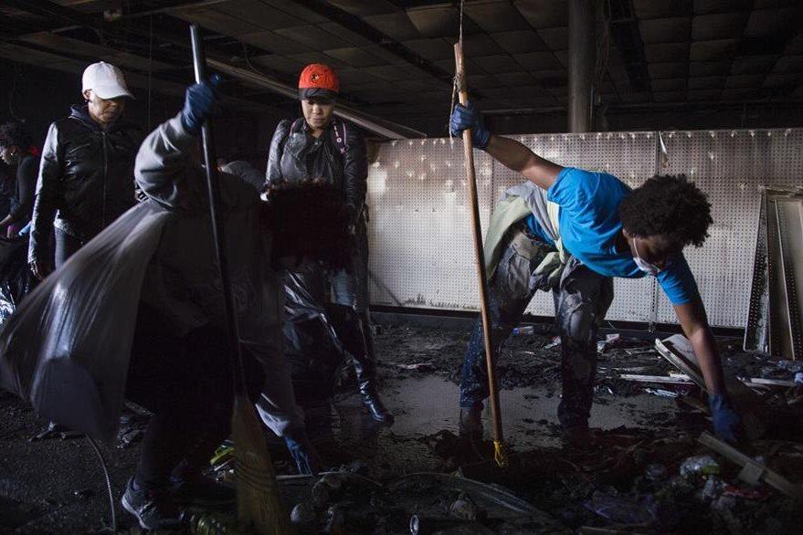 Un hombre limpia los escombros en una farmacia que fue saqueada ayer en los disturbios de Baltimore. (Foto Prensa Libre: AFP).
