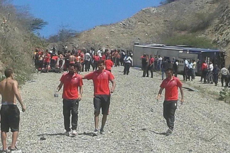 Los jugadores del Huracán de Argentina caminan en el lugar donde se accidentó el autobús en el que viajaban. (Foto Prensa Libre: AP)