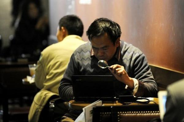 <p>Un hombre mira la pantalla de su computadora con una lupa en un café de Pekín el 2 de noviembre pasado. (AFP).<br></p>