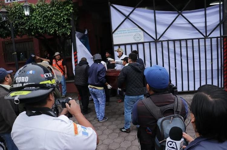 Varias personas esperan que les entreguen el cuerpo de sus familiares en la morgue provisional de San Juan Alotenango, Sacatepéquez. (Foto Prensa Libre: Víctor Chamalé)