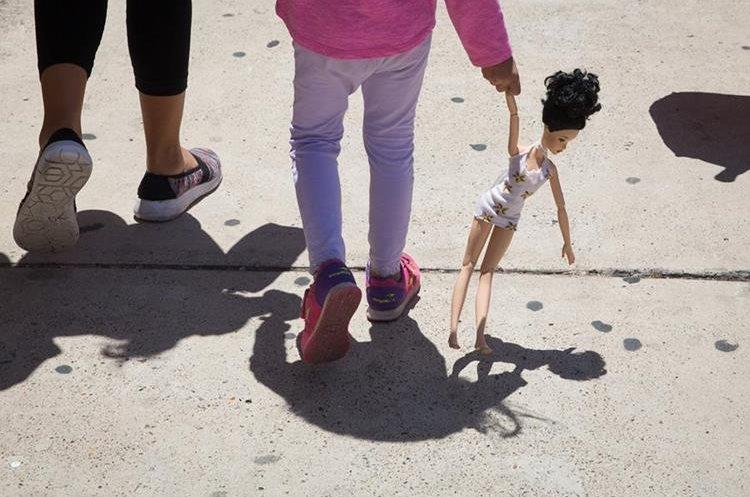 Una niña hondureña de 4 años carga una muñeca mientras camina con su madre inmigrante, ambas liberadas de un centro de socorro en McAllen. Texas. (AFP).