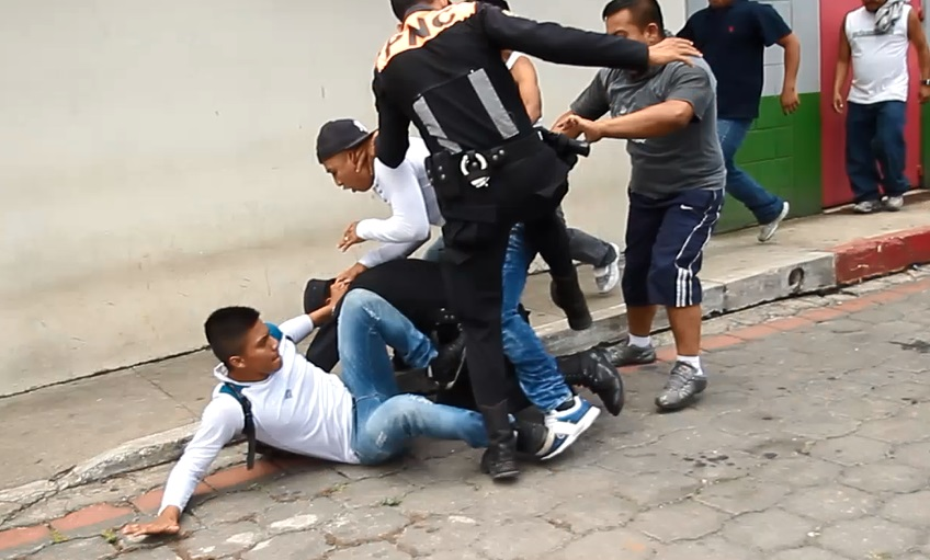Un policía -de pie- ayuda a su compañero el cual fue lanzado al piso por tres manifestantes. (Foto Prensa Libre: É. Ávila)