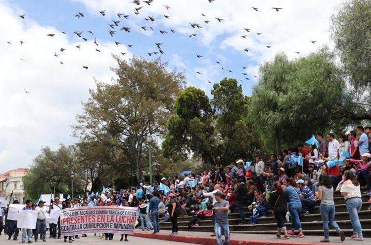 Vecinos observan el paso de la marcha en el centro de la Ciudad de Quetzaltenango. (Foto Prensa Libre: Raúl Juárez)
