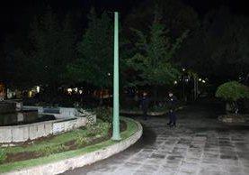 Dos agentes se distinguen entre la oscuridad en el parque de Quetzaltenango que carece de iluminación y se ha convertido en un lugar para delinquir por las noches. (Foto Prensa Libre: Carlos Ventura)