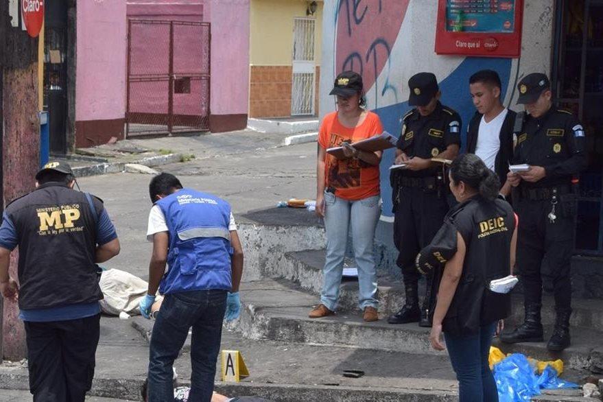 Investigadores policiales recogen evidencias en el lugar donde dos hombres fueron ultimados, en Escuintla. (Foto Prensa Libre: Carlos E. Paredes)