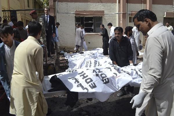 Voluntarios paquistaníes cubren los cuerpos de las víctimas de la explosión de una bomba.(Foto Prensa Libre:AFP).