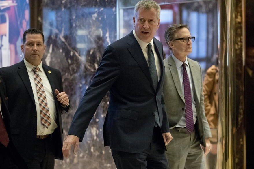 El alcalde de Nueva York, Bill de Blasio (centro) arriba al edificio donde se reunió con el presidente electo de EE. UU., Donald Trump. De Blasio aseguró que protegerá a los indocumentados. (Foto Prensa Libre: AP).