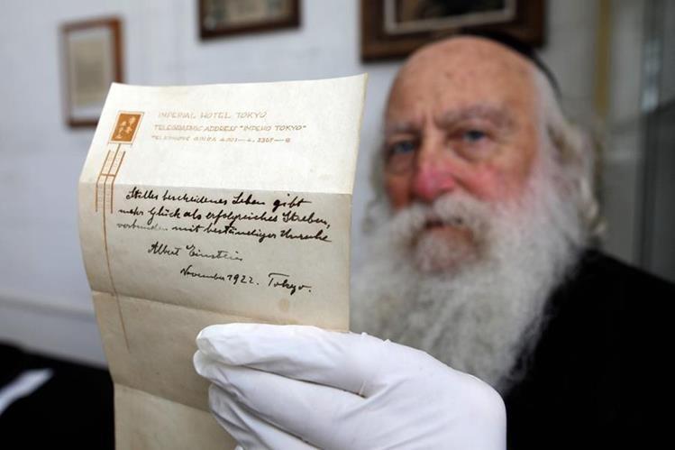 Un hombre sostiene la nota de Albert Einstein en la que escribe la Teoría de la Felicidad, que fue subastada por una cifra millonaria (Foto Prensa Libre: AFP).