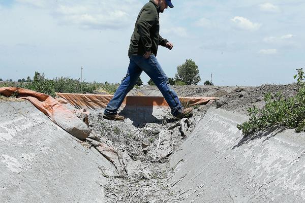 Un agricultor cruza un canal de riego que está cubierto de sal seca en Stockton, California.(Foto Prensa Libre:AP).