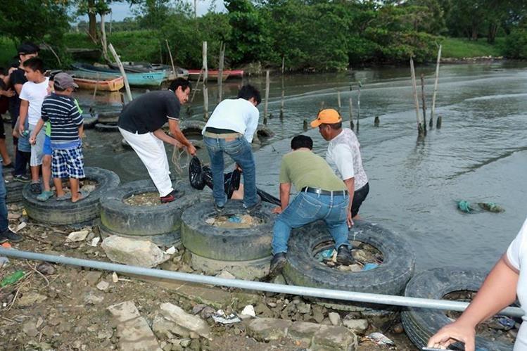 Vecinos del barrio El Limonar ayudar a extraer el cuerpo del mar. (Foto Prensa Libre: Dony Stewart)