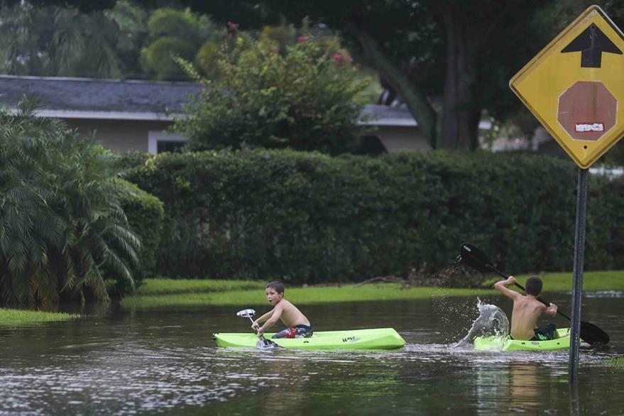 John Johnson, 8, izquierda, y Joey Brooks, 12, juegan en un vecindario inundado en Florida. (Foto Prensa Libre AP).