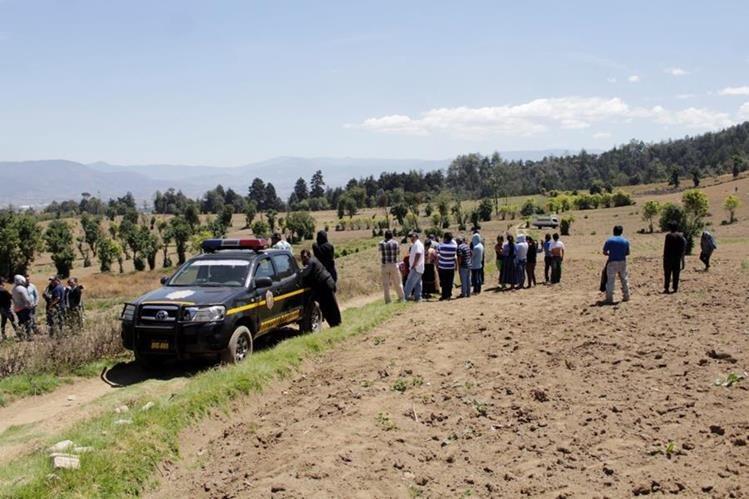 Vecinos de San Mateo, Quetzaltenango, observan el lugar donde fue hallado el cuerpo de una mujer con señales de violencia. (Foto Prensa Libre: María José Longo)