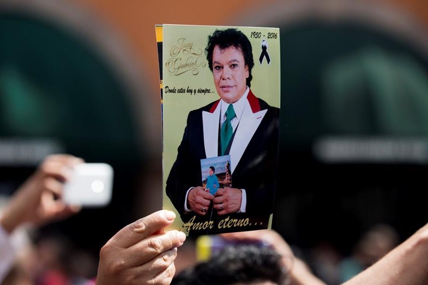 Seguidores de Juan Gabriel muestran imagen del compositor y cantante mexicano al lado de una estatua de él en la plaza de la Ciudad de México. (Foto Prensa Libre: AP)