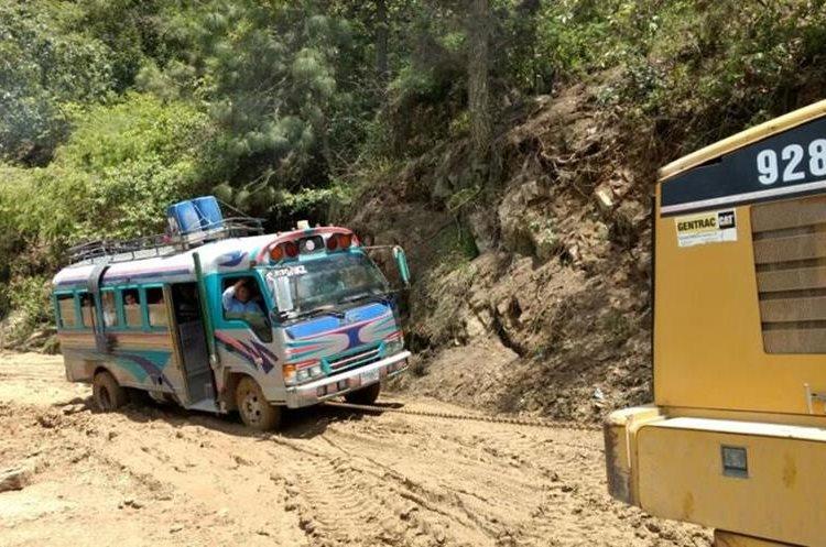 Maquinaria que arregla tramo en ruta a San Andrés Sajcabajá, Quiché, remolca un microbús que se quedó atascado por el mal estado de la vía. (Foto Prensa Libre: Héctor Cordero)