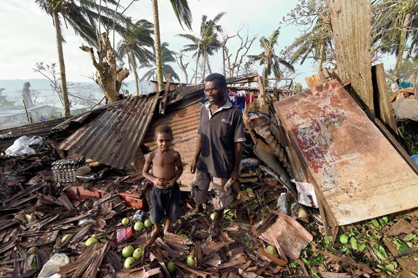 Un niño y su padre buscan rescatar algo de su casa en ruinas, tras el paso de Pam en Vanuetu. (Foto Prensa Libre: AFP).
