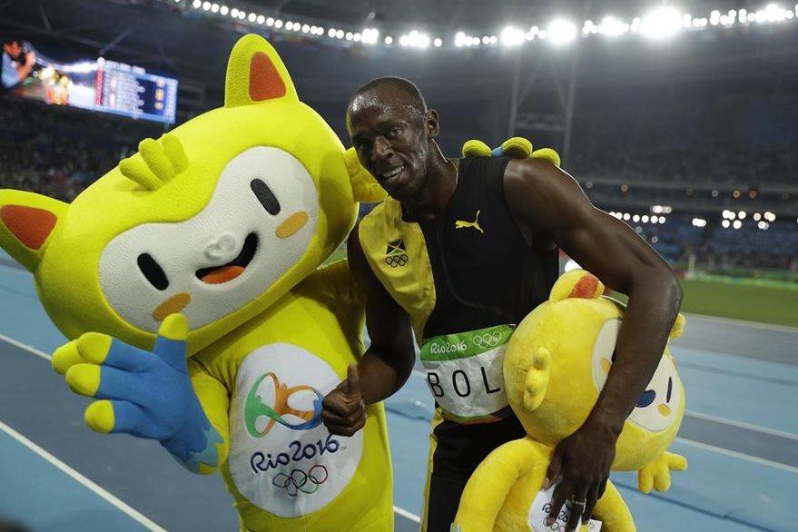 Bolt celebra el oro con la mascota de Río 2016. (Foto Prensa Libre: AP)