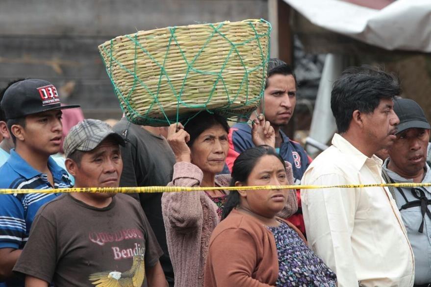 Comerciantes del mercado La Terminal observan el cadáver del hombre, atacado a balazos mientras compraba fruta. (Foto Prensa Libre: Erick Ávila)