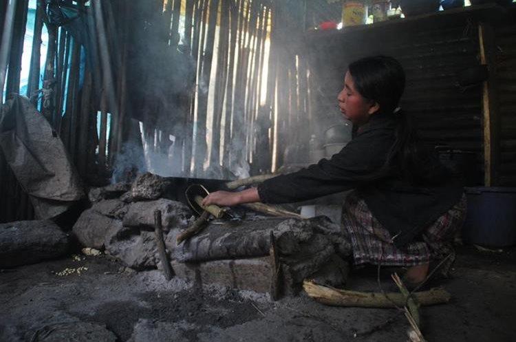 """Juana Juan José, duerme en el suelo, en su covacha construida de palos y láminas viejas, junto a sus dos hijos, con frecuencia padecen de catarros que al complicarse se han convertido en neumonías, no solo por al frío en su comunidad Payá, Jacaltenango, Huehuetenango, sino por la inhalación del humo del fuego con el que prepara sus alimentos en la misma habitación.  Basura y leña es el combustible que utiliza para poder cocinar, sus condiciones de extrema pobreza, no le permiten tener acceso a una estufa de gas, por lo que pese a estar consiente que el humo causa daños en su salud, se adapta a convivir con """"el enemigo en casa"""".  La joven madre, asegura que el gasto en leña es fuerte, entre sus tareas debe buscar en las montañas de la comunidad, pues no se trata solo de fuego sino calor para mitigar el frío, sobre todo en épocas de invierno."""