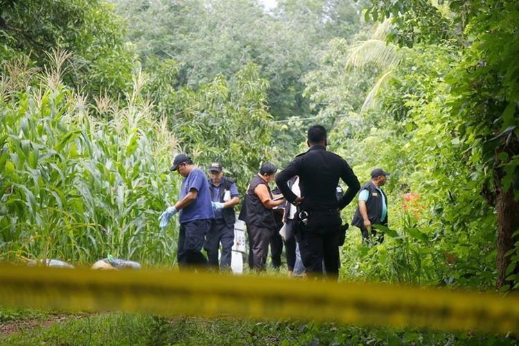Oficiales de PNC inspeccionan el área donde hallaron los dos cuerpos. (Foto Prensa Libre: Rolando Miranda)