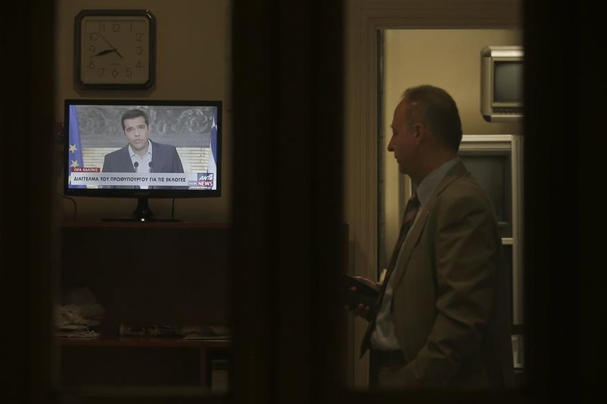 Un hombre observa el mensaje televisado del primer ministro griego Alexis Tsipras donde anunció su dimisión. (Foto Prensa Libre: AP).
