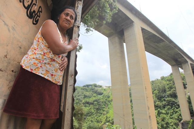 Vera Luz Flores, de 52 años, observa el fondo del barranco  ubicado debajo del puente El Incienso. Desde hace 12 años vive así  en el asentamiento Santa Rita. (Foto Prensa Libre: Esbin García)