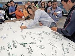 Colaboradores de Prensa Libre firman una gigantesca manta en donde plasman diversidad de valores que no cambiarán en este medio de comunicación. (Foto Prensa Libre)