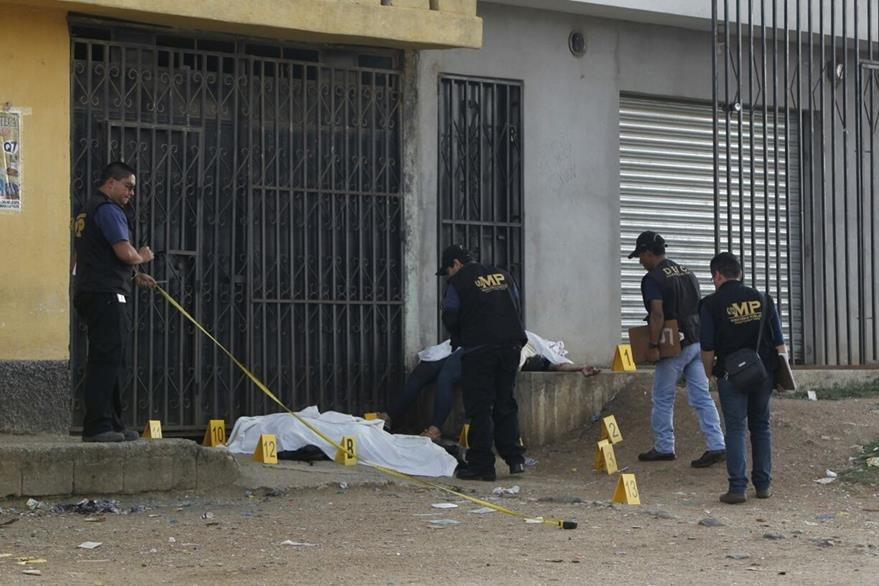 Peritos del MP recolectan evidencia alrededor de los cuerpos, en San Pedro Ayampuc. (Foto Prensa Libre: Paulo Raquec)