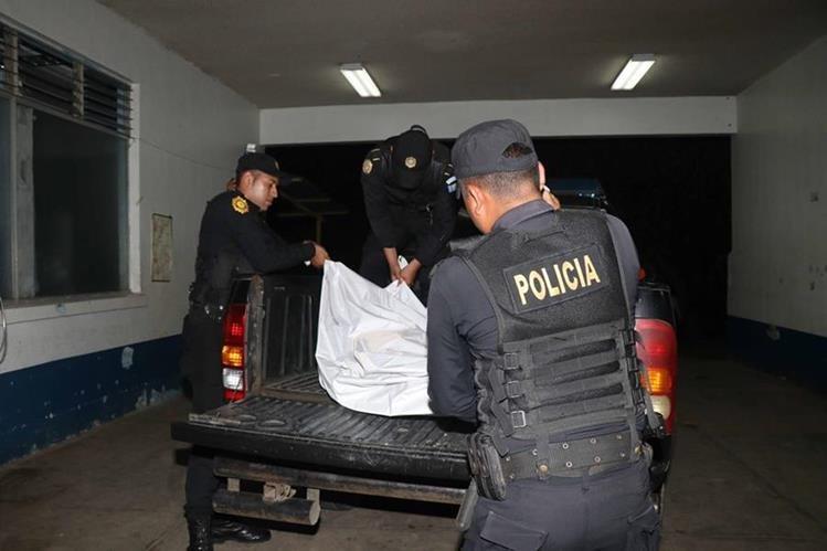 Agentes de la Policía Nacional Civil trasladan los cuerpos de dos hombres linchados en San Marcos Palajunoj, El Palmar, Quetzaltenango. (Foto Prensa Libre: Rolando Miranda)