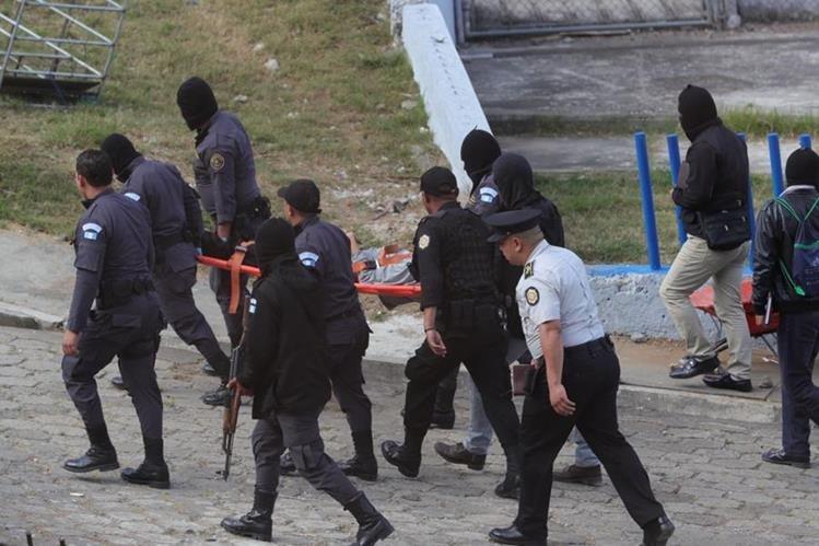 Guardias del Sistema Penitenciario retiran los cadáveres de los cuatro reos muertos hallados en el Preventivo de la zona 18. (Foto Prensa Libre: Estuardo Paredes)