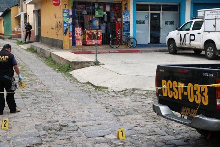 Fiscales del MP recogen evidencia en el lugar donde ocurrió el ataque contra un autobús urbano, en la zona 1, de Xela. (Foto Prensa Libre: Carlos Ventura)