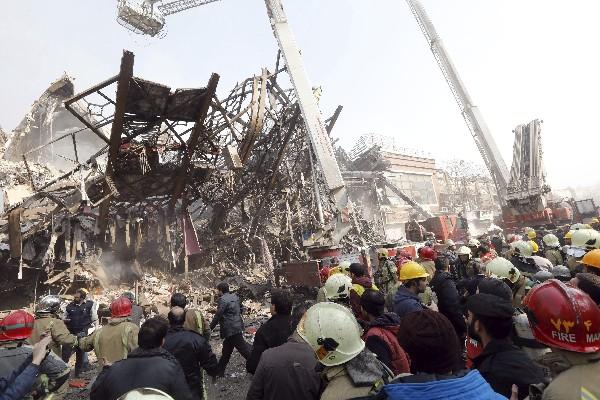 Bomberos iraníes buscan sobrevivientes en el edificio derrumbado en el centro de Teherán. (Foto Prensa Libre: EFE)