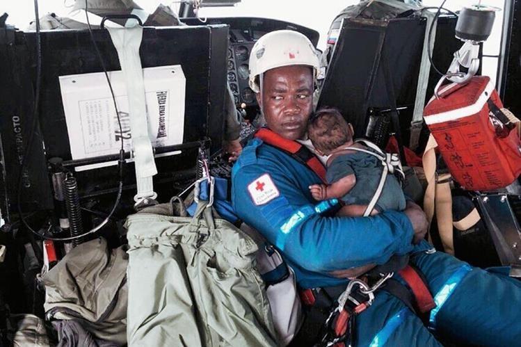 """Ascisclo Rentería, el """"héroe"""" colombiano sostiene en brazos al bebé que fue rescatado tras permanecer cinco días perdido en la selva con su madre. (Foto Prensa Libre: AFP)."""