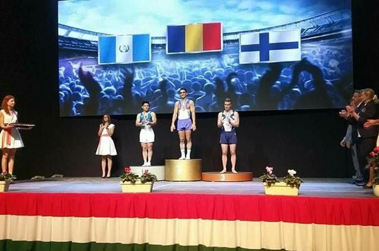 Vega junto al rumano Marian Dragulescu en el podio de la Copa del Mundo en Hungría. (Foto Prensa Libre: Facebook)