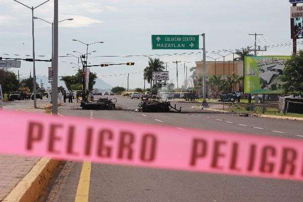 Vista de vehículos quemados (d) del convoy militar emboscado en Culiacán, Sinaloa, México.(AFP).