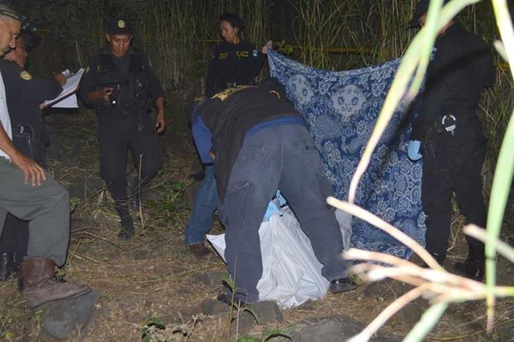 Agentes fiscales del Ministerio Público cubren el cuerpo de Ángel Pérez, en Asunción Mita, Jutiapa. (Foto Prensa Libre: Óscar González)