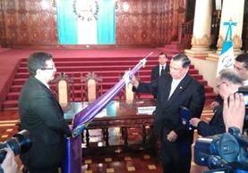Fuentes Soria coloca las insignias de la Orden del Quetzal a la bandera de la Facultad de Odontología. (Foto Prensa Libre: Geovanni Contreras)