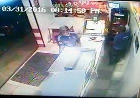 Momento en el que los dos individuos asaltan el negocio en Cobán. (Foto Prensa Libre).
