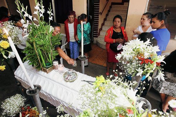 Blanca Azucena Cuté ( suéter rojo) madre del niño, durante el velatorio.( Foto Prensa libre: hemeroteca pl)