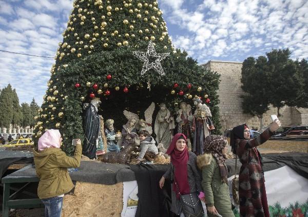 Varias musulmanas se toman fotos delante de un belén cerca de la Basílica de la Natividad.(EFE).