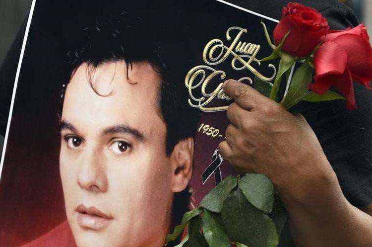 Un seguidor de Juan Gabriel toma en sus manos un póster alusivo al homenaje (AFP).