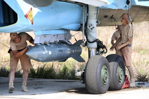 Militares rusos colocan una bomba guiada a un avión de combate SU-34.