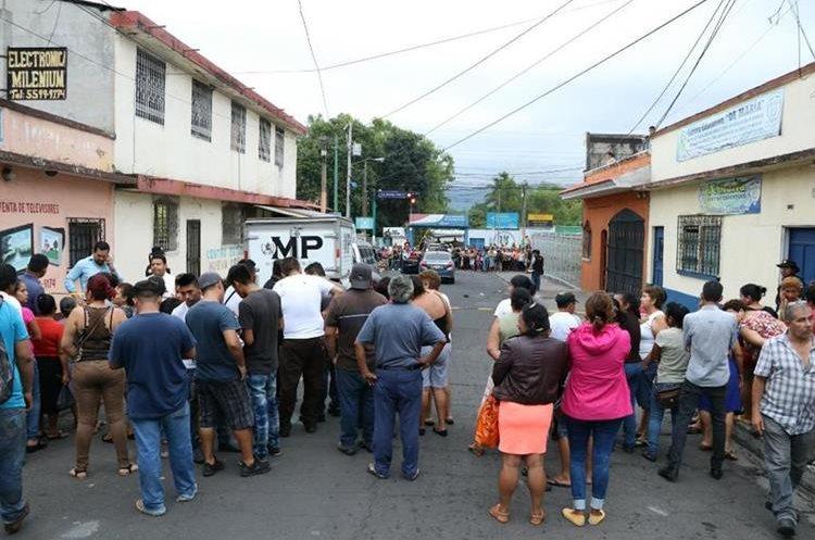Curiosos se aglomeran cerca del lugar donde murió baleada la abogada Ana Beatriz Figueroa, en la zona 1 de Escuintla. (Foto Prensa Libre: Enrique Paredes)