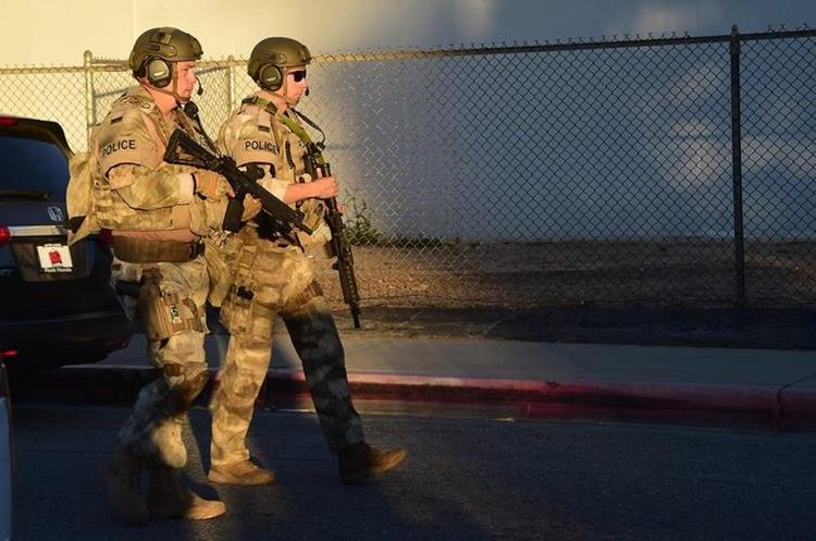 Swat police walk along closed off streets in the San Bernardino neighborhood near the intersection of Richardson and Gould where a house was searched on December 2, 2015.   A man and a woman suspected of carrying out a deadly shooting at a center for the disabled in California were killed in a shootout with police, while a third person was detained, police said. AFP PHOTO / FREDERIC J. BROWN