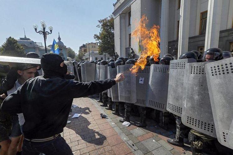 Un manifestante amenaza a los policías que resguardan el parlamento uraniano después de los graves disturbios. (Foto Prensa Libre: EFE).