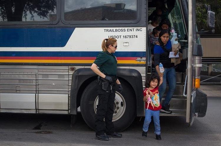 Grupo de inmigrantes son dejados en una estación de autobuses poco después de ser liberados en McAllen, Texas. (AFP).