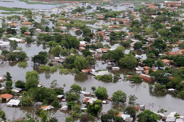 ASU08. ASUNCIÓN (PARAGUAY), 28/12/2015.- Vista de varias viviendas que quedaron bajo el agua por las inundaciones en un barrio de Asunción (Paraguay) hoy, lunes 28 de diciembre de 2015. La cifra de evacuados por las crecidas del río Paraguay a su paso por Asunción asciende a 100.000 personas, mientras que hay cerca de 10.000 desplazados en el sureño departamento de Ñeembucú, adonde hoy viajó el presidente paraguayo, Horacio Cartes, para conocer de cerca la situación. EFE/Andrés Cristaldo Benítez