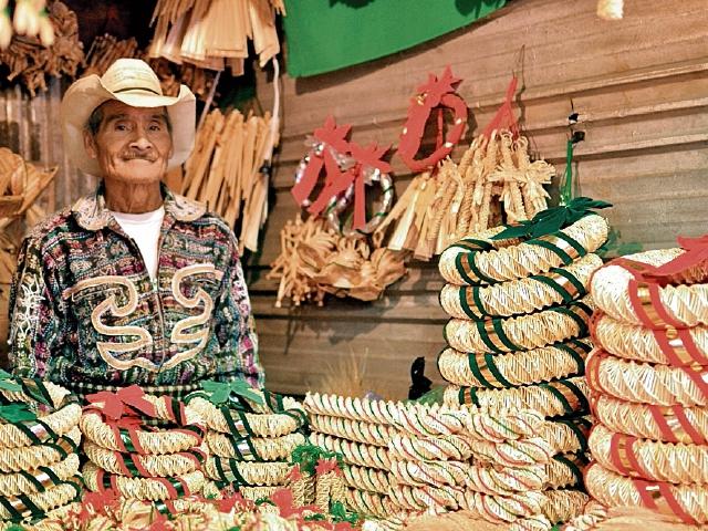 """Don Margarito Bocel ya cumplió 30 años de viajar desde El Tablón, Sololá, hasta Ciudad Capital para vender adornos elaborados de paja de trigo. """"Vamos a Nahualá para comprar el trigo y en agosto comenzamos a hacer los adornos"""", dice Bocel, quien afirma que esta es una tradición familiar que le ayuda económicamente."""