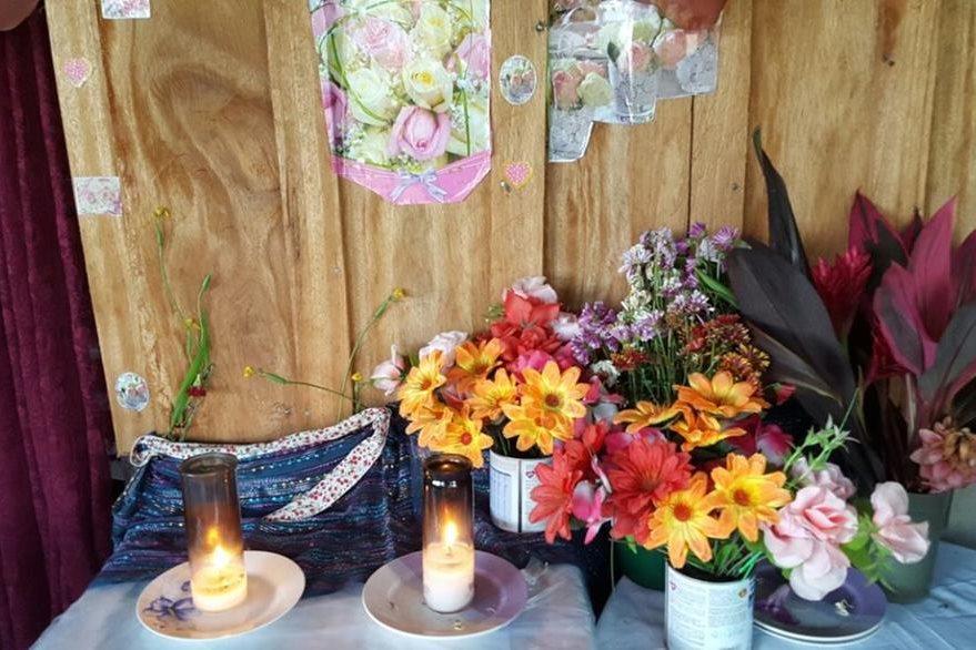 Veladoras y flores son colocadas en un altar elaborado por una mujer en Poptún, quien asegura haberse curado de una enfermedad luego de la aparición de una imagen religiosa. (Foto Prensa Libre: Walfredo Obando)
