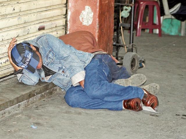 Una persona  sin hogar  duerme frente a un comercio en San Pedro Sacatepéquez, San Marcos. (Foto Prensa Libre: Aroldo Marroquín)